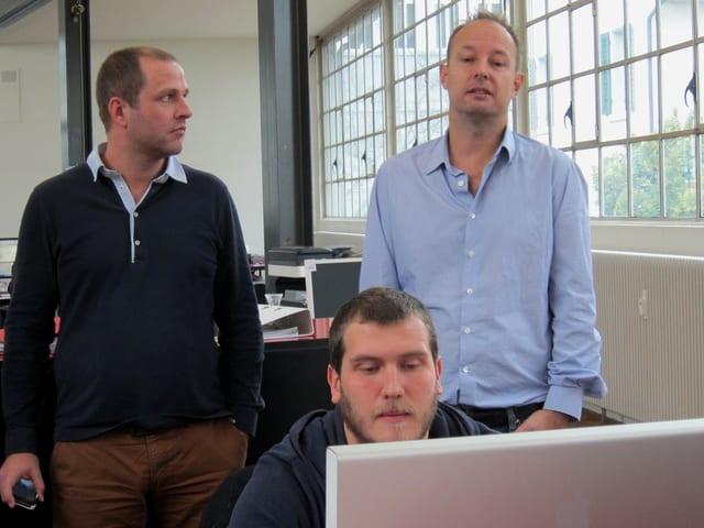 Ein Mann sitzt am Pult vor einem Computer, hinter ihm stehen zwei weitere Männer, von denen einer ebenfalls auf den Bildschirm schaut.