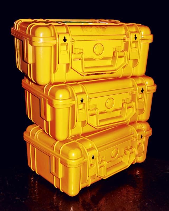 Drei gelbe Koffer, aufeinandergestapelt.