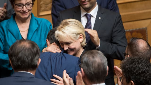 Moret umarmt Cassis von applaudierenden Parlamentariern umgeben.