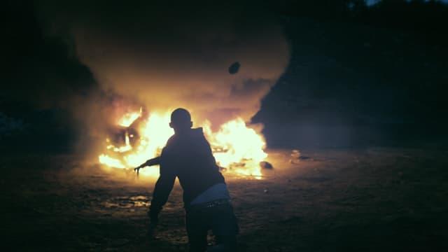 Szene: Ein junger Mann vor einem grossen Feuer.