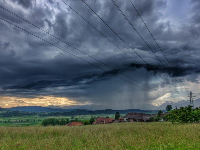 Starker Regen fällt aus schwarzer Wolke