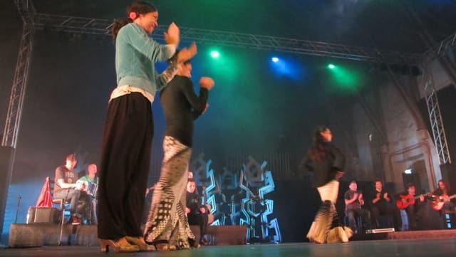 2 Frauen klatschen vorne im Rhytmus, hinten wird getanzt und musiziert.