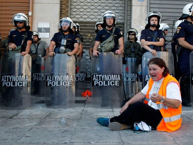 Eine Frau sitzt am Boden und ruft, hinter ihr stehen Polizisten in Kampfmontur.
