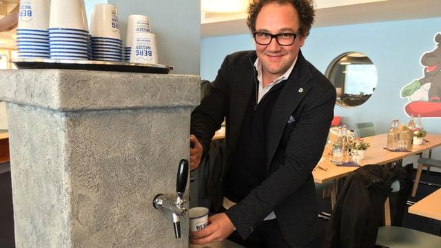 Ein Mann, welcher an einem Brunnen einen Becher mit Wasser füllt.