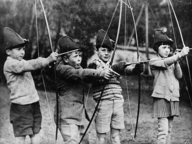 Schwarz-weiss-Aufnahme von 4 Kindern. Sie tragen einen Hut und halten einen Pfeilbogen in der Hand.