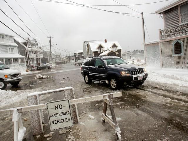 Zwei Fahrzeuge auf einer eisigen, gesperrten Strasse in Scituate, Massachusetts.