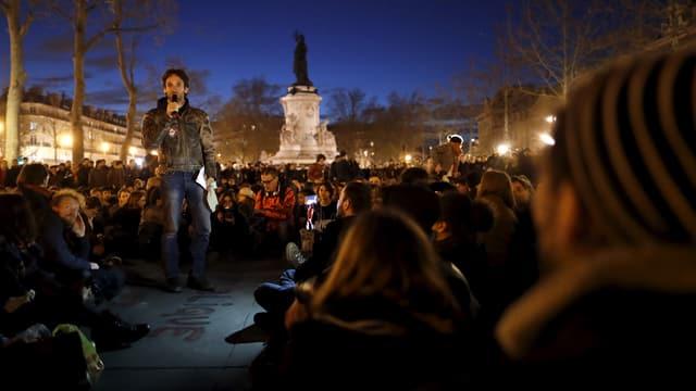 Menschen sitzen in der Abenddämmerung am Boden, ein Mann in Lederjacke udn Jeans steht dazwischen und spricht in ein Mikrofon.