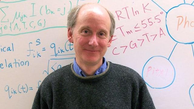 Ein Mann im grauen Pulli vor einer mit Formeln beschriebenen Wand.