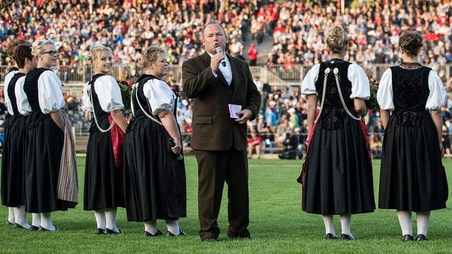 OK-Präsident Andreas Aebi spricht umgeben von Ehrendamen in der Arena zu den Besuchern.