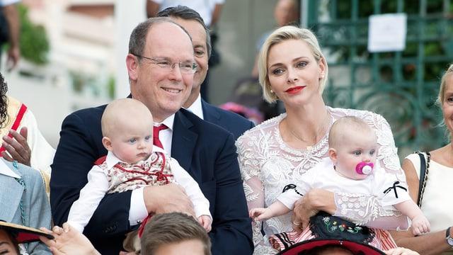 Fürst Albert im Anzug mit Sohn Jacques auf dem Schoss, neben ihm Charlène im weissen Kleid mit Tocheter Gabriella im Schoss.