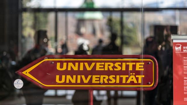 Ein Pfeil, zweisprachig angeschrieben, weist den Weg zur Universität.