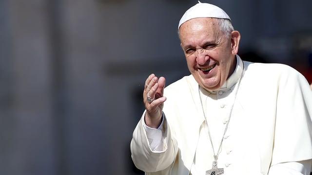 Papst Franziskus in einem weissen Gewand. Er lächelt und winkt.