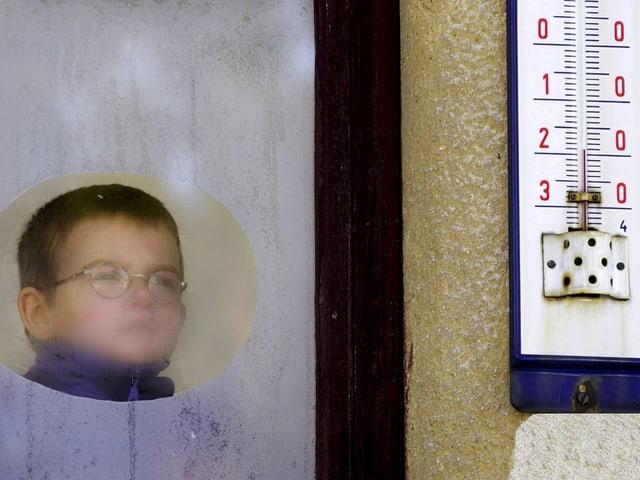 Ein kleiner Junge steht vor einem Fenster. Es ist von der Feuchtigkeit beschlagen. Draussen an der Hauswand ist ein Thermometer zu sehen. Es zeigt -20 Grad.