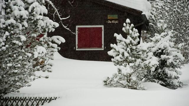 Ein verschneites Ferienhaus mit geschlossenen Fenstern.