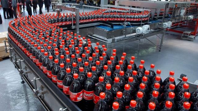 Coca-Cola-Flaschen stapeln sich auf der Abfüllanlange.