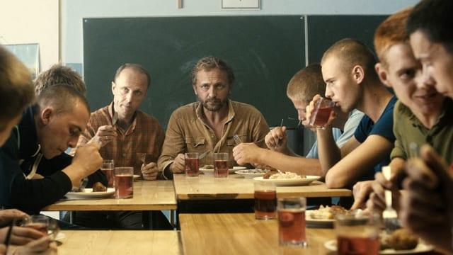 Rund um einen Tisch sind jüngere und zwei ältere Männer zum Essen versammelt.
