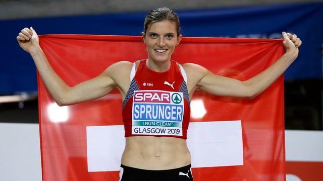 L'atleta Lea Sprunger cun la bandiera svizra.