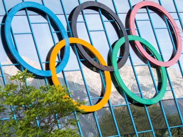 Die Olympischen Ringe auf einer Glas-Fassade