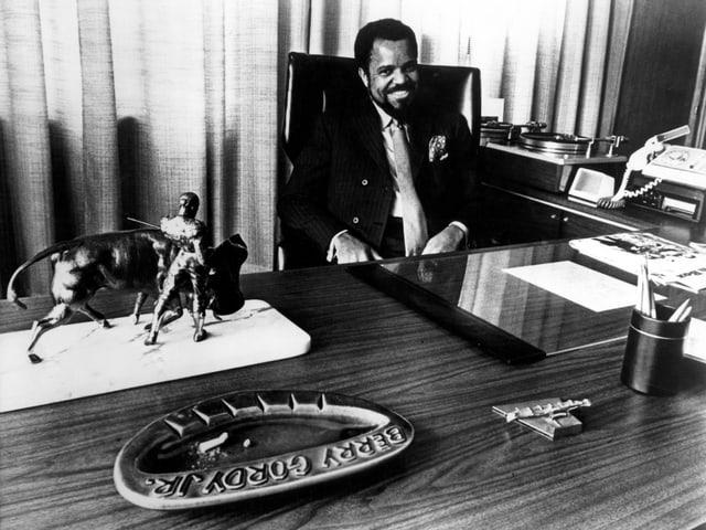 Ein Mann sitzt lachend an einem grossen Schreibtisch.