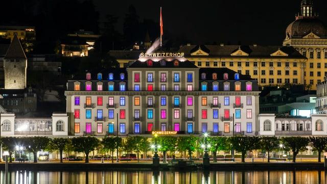 Ein grosses Haus, bei welchem die Fenster farbig beleuchtet sind von innen.