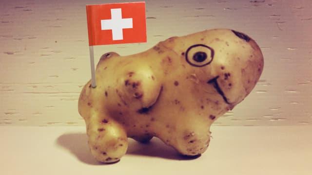 Eine Kartoffel in Hundeform mit einer eingespickten Schweiz-Flagge.