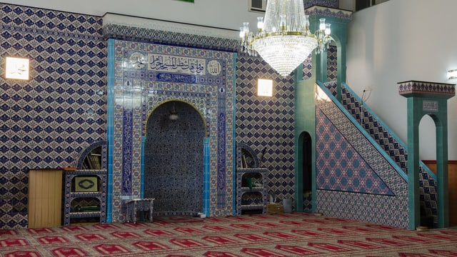 Der Gebetsraum in der bosnischen Moschee Emmenbrücke mit Gebetsnische und Predigtkanzel.
