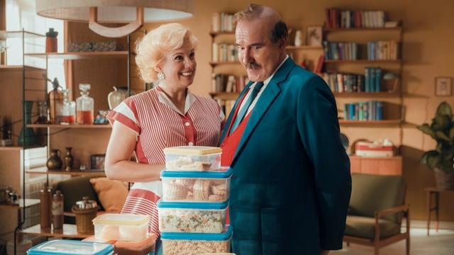 Szenen in einer altmodisch eingerichtete Wohnung: Eine Frau mit Dauerwelle schaut ihren Mann erfreut an. Er steht neben ihr und schaut vor sich auf den Tisch. Dort stehen unzählige Plastikboxen in verschiedenen Grössen, alle gefüllt mit Essen. Darunter Teigwaren, Pastetli oder Wähenstücke.