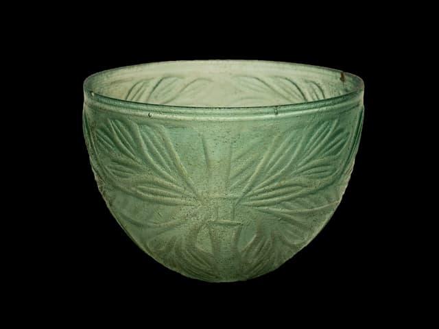 Eine grünlich schimmernde Glasschale, verziert mit Blattmustern.