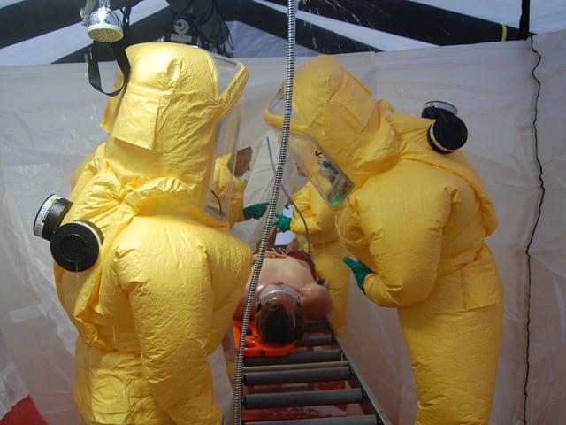 Menschen in gelben Vollschutz-Anzügen waschen einen Patienten.