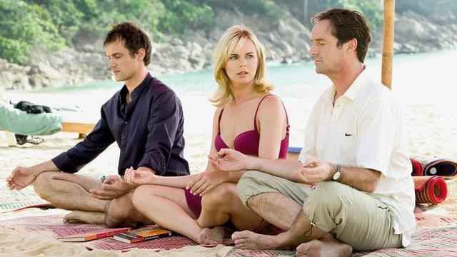 2 Männer und eine Frau (in der Mitte) mache Yoga (Ohm!) am Strand.
