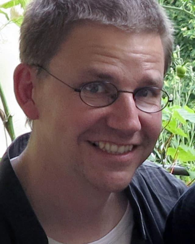 Junger Mann mit kurzem Haar und Brille.