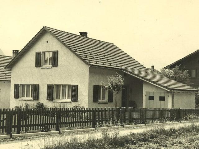 Schwarz-Weiss-Fotografie von einem Zweifamilienhaus mit Garten.