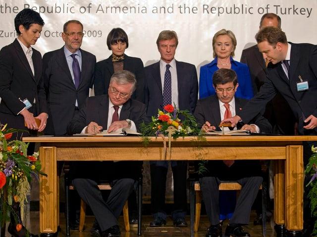 Frauen und Männer stehen hinter einem Tisch, an dem zwei Männer ein Dokument unterzeichnen.