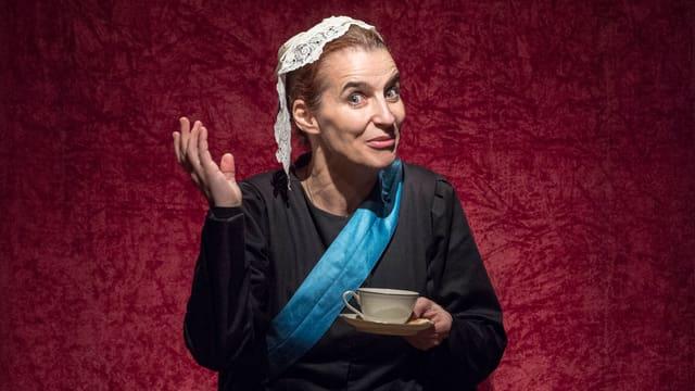 Eine Frau mit Kopfbedeckung gestikuliert mit einer Tasse in der Hand.