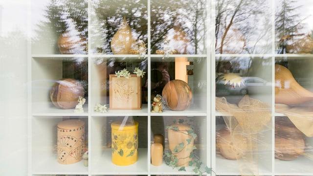 Ein Schaufenster mit Holzurnen, in dem sich Bäume spiegeln.