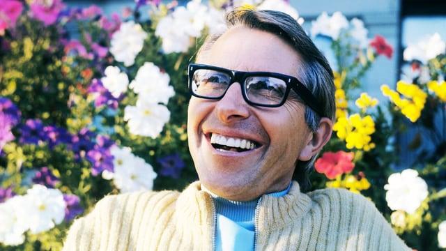 Armin Schibler sitzt lachend vor bunten Blumen.