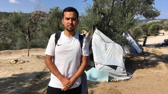Junger Mann mit weissem T-Shirt, der vor einem kaputten Zelt steht.