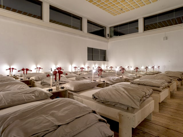 56 Betten in einem Ausstellunsraum: Sie sind weiss bezogen und schumrig beleuchtet.