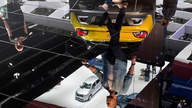Menschen spiegeln sich im Boden am Autosalon Genf, inmitten von Autos.