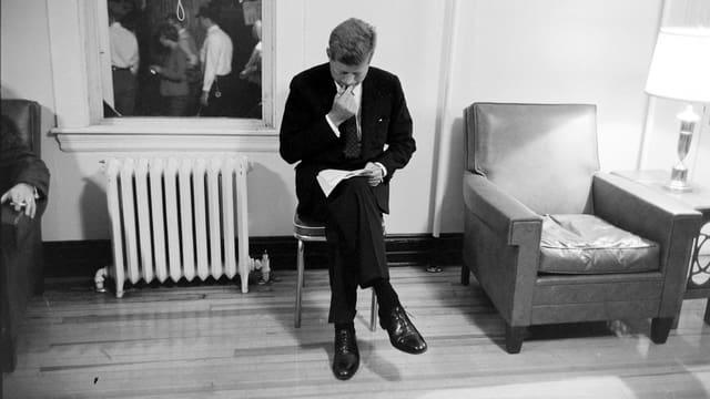 Kennedy sitzt auf einem Stuhl über Papiere gebeugt.