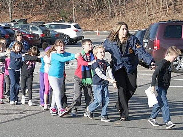 Kinder über Parkplatz gehend, begleitet von einer Polizistin