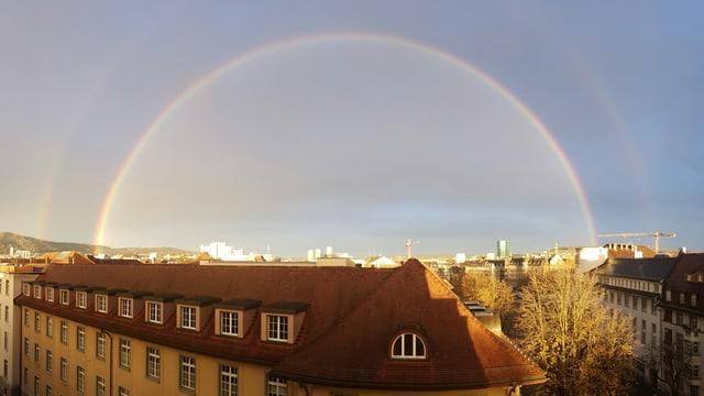 Ein Regenbogen über den Dächern der Stadt.