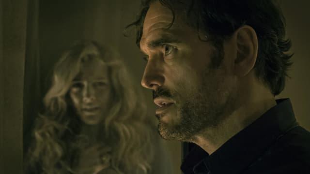 Ein Mannund eine Frau in einem dunklen Raum.