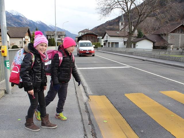 Zwei Kinder stehen an einem Fussgängerstreifen, im Hintergrund ein Auto.