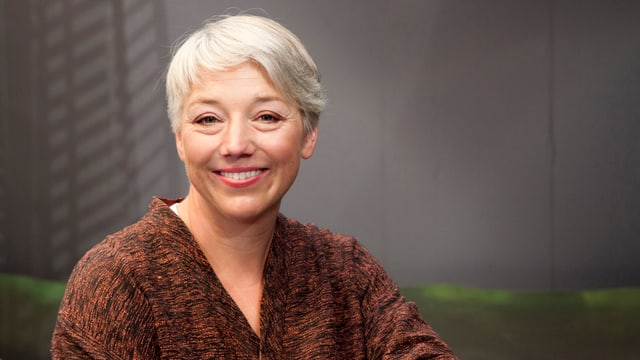 Andrea Kuster im Porträt. Sie hat kurzes blondes Haar.