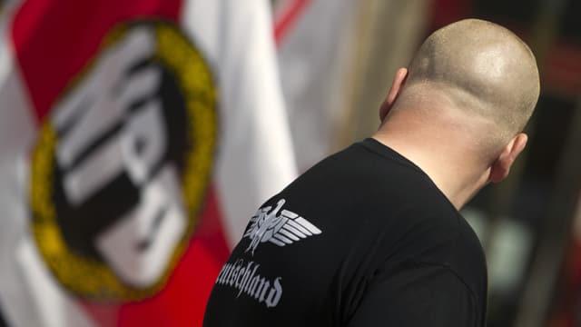 Skinhead vor NPD-Fahne.