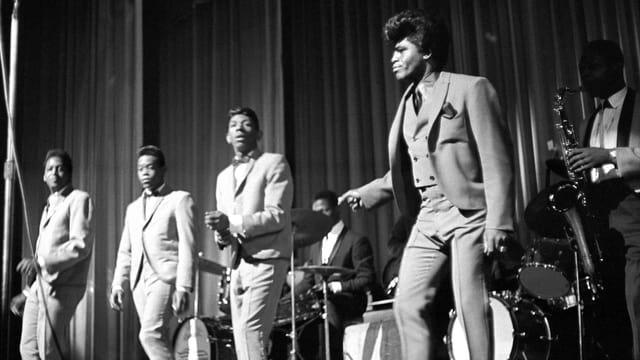 James Brown (rechts) tritt mit den Famous Flames (Johnny Terry, Bobby Byrd, Bobby Bennett) 1964 im Apollo auf.