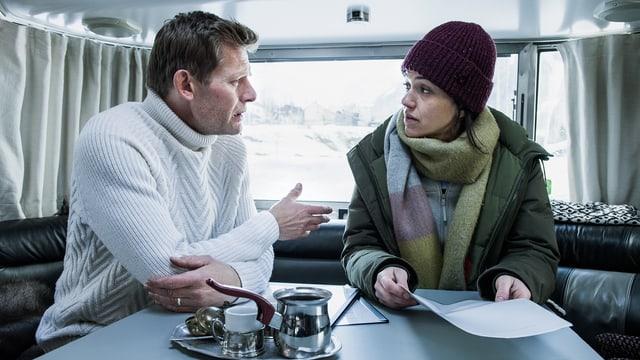 Ein Frau und ein Mann sprechen miteinander in einem Wohnwagen. Sie trägt Winterkleidung mit Wollmütze und hlät ein Papier in der Hand,