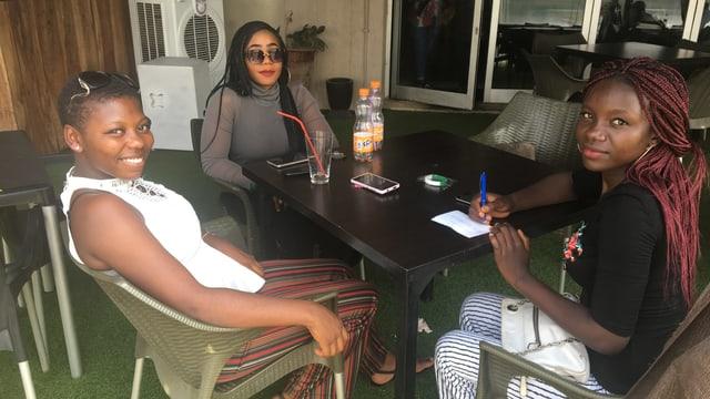 Drei junge Frauen an einem Tischchen