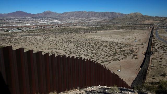 Grenzzaun zwischen den USA und Mexiko von einem Hügel aus in die Wüste herab fotografiert, im Hintergrund Berge